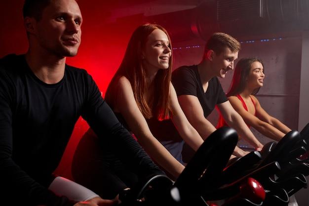 Jovens andando de bicicleta na aula de spinning em uma academia moderna, fazendo exercícios em bicicleta ergométrica. forte treinamento masculino e feminino em bicicleta ergométrica