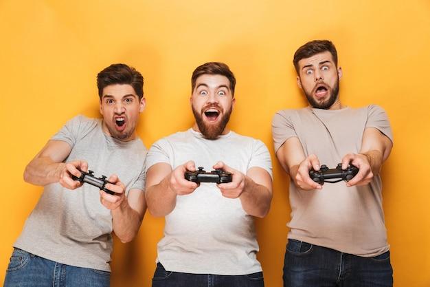 Jovens animados, amigos de homens jogam com joysticks.