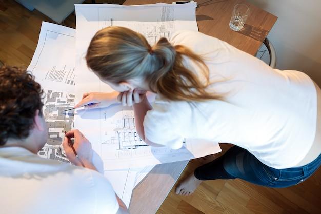 Jovens arquitetos trabalhando com mapa e blueprint
