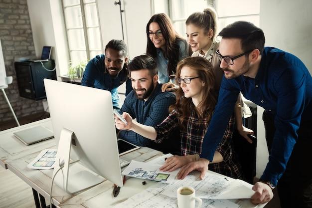 Jovens arquitetos trabalhando juntos em projeto em escritório
