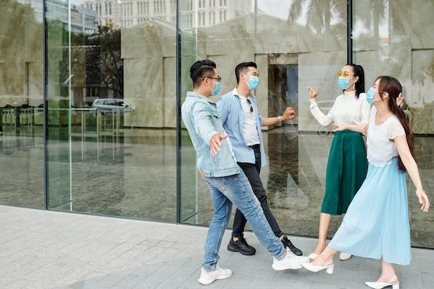 Jovens asiáticos alegres com máscaras protetoras, tocando os dedos dos pés uns nos outros em vez de dar mais um toque
