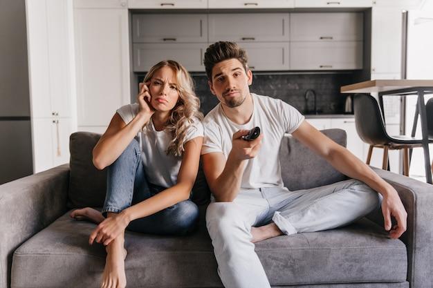 Jovens assistindo filme. casal curtindo programa de tv.