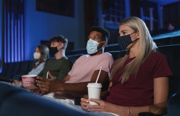 Jovens assistindo filme no cinema, conceito de coronavírus.