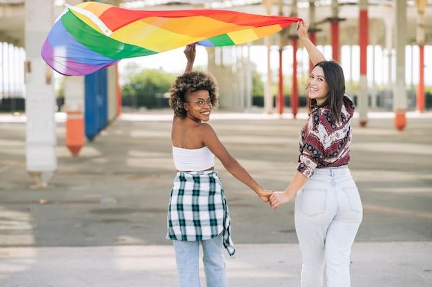 Jovens ativistas sorrindo e segurando a bandeira do arco-íris, símbolo do movimento social lgbti