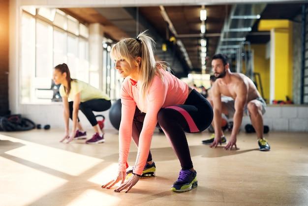 Jovens atletas cansados em uma academia, esticando os músculos das pernas após a aula de pilates.
