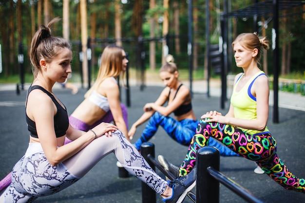 Jovens atletas do sexo feminino alongamento antes de correr no parque