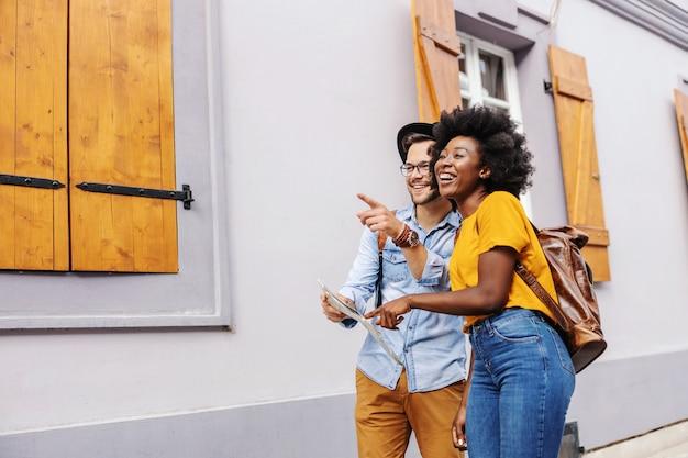 Jovens atraentes turistas multiculturais andando na rua e olhando para belos edifícios. mulher apontando para o mapa enquanto o homem apontando para algo.