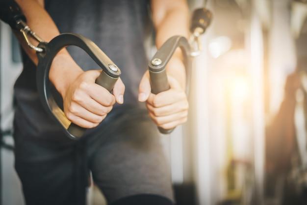 Jovens atrativos rasgado bodybuilder malhando na academia.