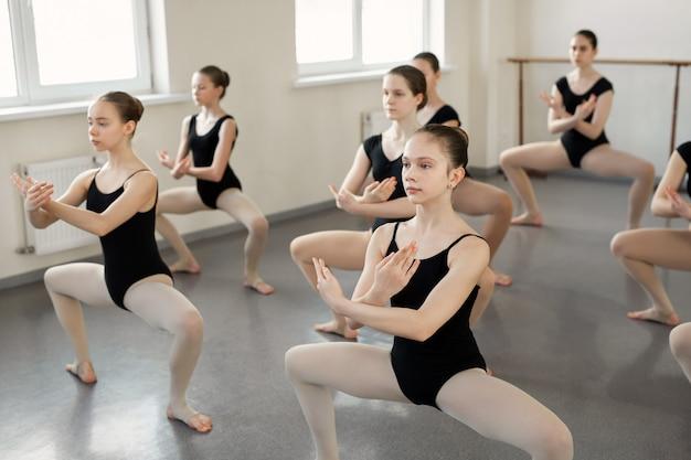 Jovens bailarinas fazem exercícios complexos na escola de balé