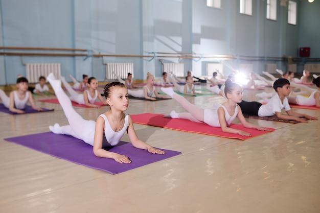 Jovens bailarinos no estúdio de balé. jovens bailarinos executam exercícios de ginástica durante um aquecimento na sala de aula. esporte, ginástica, desenvolvimento infantil