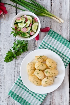 Jovens batatas cozidas com manteiga e endro em um prato branco