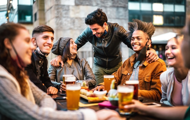 Jovens bebendo cerveja com máscara facial aberta