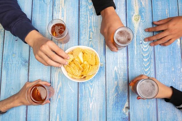 Jovens bebendo cerveja e se divertindo à mesa