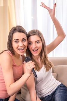 Jovens beldades cantam uma canção em casa.