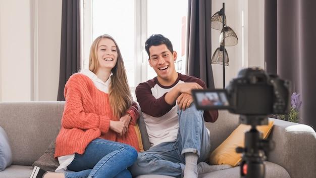 Jovens blogueiros de vídeo se divertindo juntos e criando conteúdo enquanto fazem um vídeo em casa