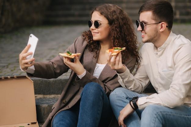 Jovens blogueiros fazem selfie com uma fatia de pizza nas mãos