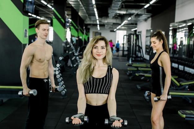 Jovens bombeando músculos com halteres. garota loira e bonita aptidão exercitando com barra no ginásio junto com seus amigos, mulher e homem no desgaste do esporte
