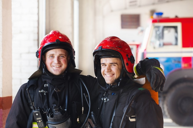 Jovens bombeiros no fundo de carros de bombeiros