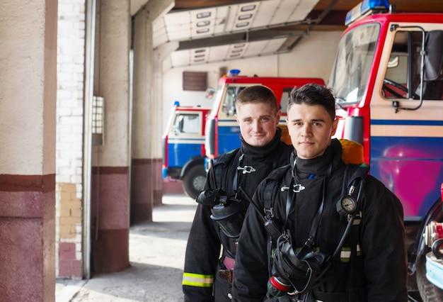 Jovens bombeiros sobre os carros de bombeiros