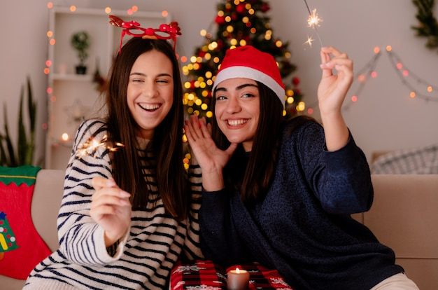 Jovens bonitas alegres com óculos de rena e chapéu de papai noel segurando e olhando fogos de artifício sentados em poltronas e curtindo o natal em casa