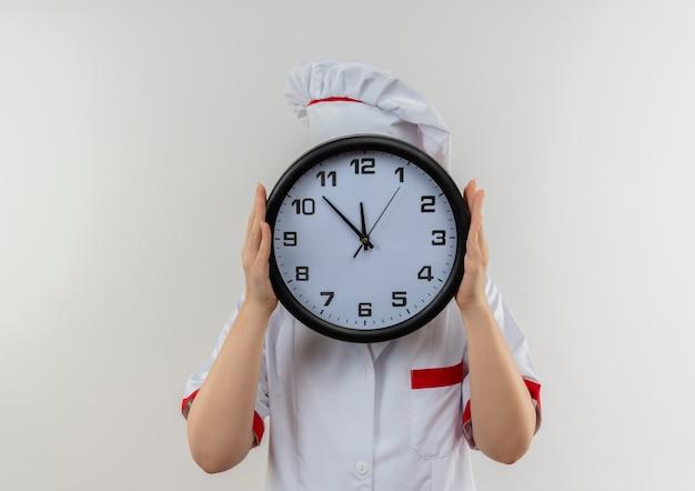 Jovens bonitas cozinheira em uniforme de chef segurando o relógio e se escondendo atrás dele