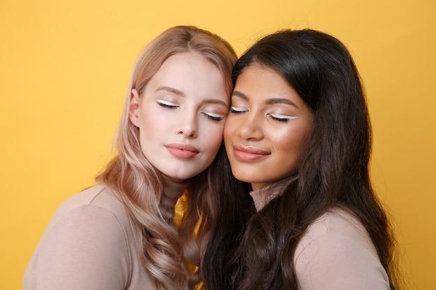 Jovens bonitas duas senhoras que estão sobre a parede amarela