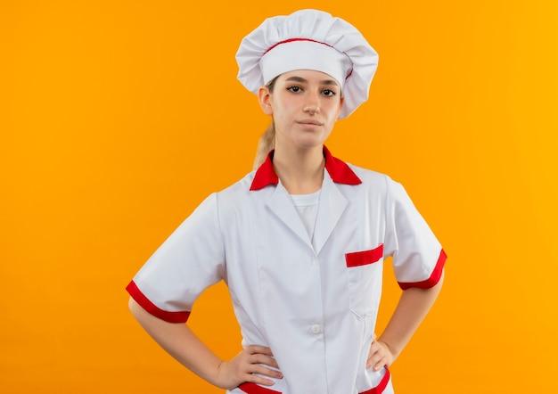 Jovens bonitas e confiantes cozinheira com uniforme de chef, colocando as mãos na cintura, isolada na parede laranja
