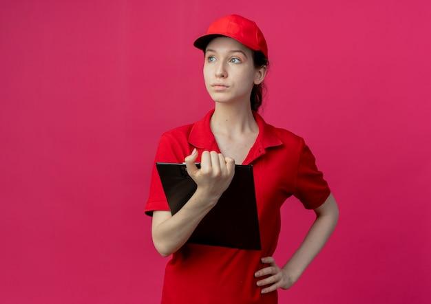 Jovens bonitas entregadores de uniforme vermelho e boné segurando a prancheta e olhando para o lado com a mão na cintura isolada em um fundo carmesim com espaço de cópia