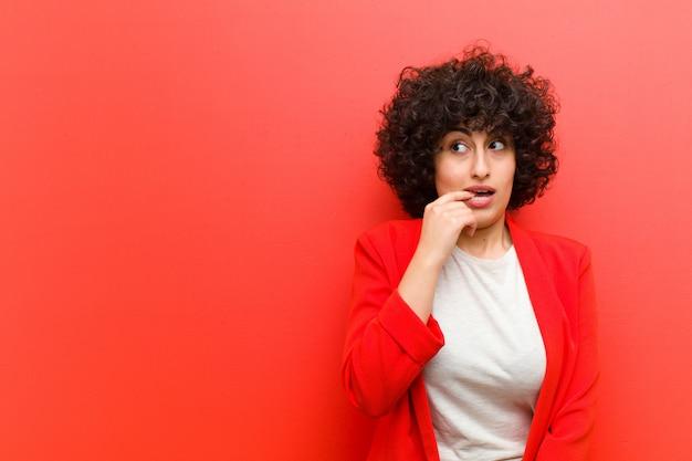 Jovens bonitas mulher afro com olhar surpreso, nervoso, preocupado ou assustado, olhando para o lado em direção copyspace