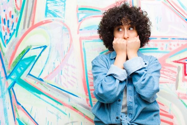 Jovens bonitas mulher afro olhando preocupado, ansioso, estressado e com medo, roer unhas e olhando para o espaço da cópia lateral contra a parede do graffiti