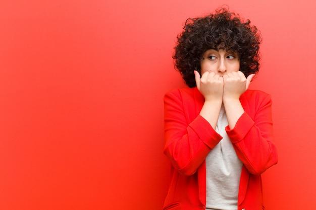 Jovens bonitas mulher afro olhando preocupado, ansioso, estressado e com medo, roer unhas