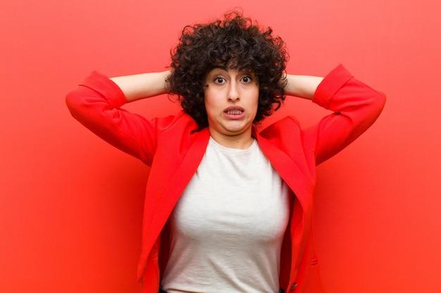 Jovens bonitas mulher afro sentindo estressado, preocupado, ansioso ou assustado, com as mãos na cabeça, em pânico por engano