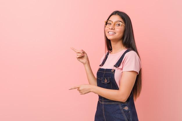 Jovens bonitas mulher árabe vestindo um jeans dungaree animado apontando com o dedo indicador fora.