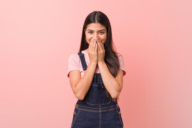 Jovens bonitas mulher árabe vestindo uma calça jeans rindo de algo, cobrindo a boca com as mãos.