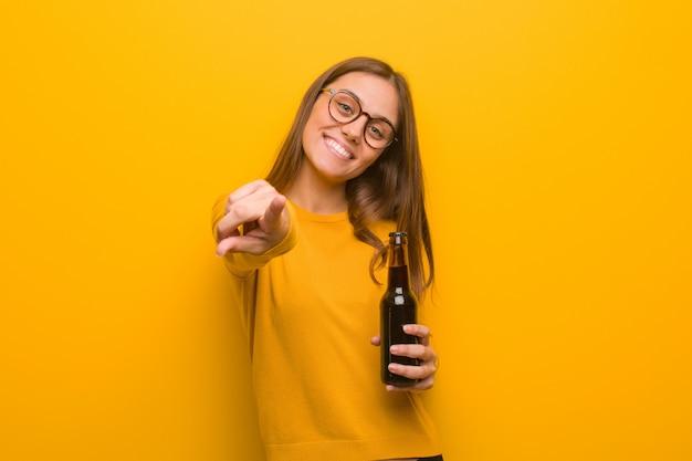 Jovens bonitas mulher caucasiana alegre e sorridente apontando para a frente. ela está segurando uma cerveja.