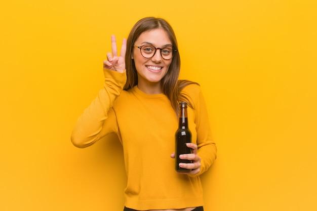 Jovens bonitas mulher caucasiana divertida e feliz fazendo um gesto de vitória. ela está segurando uma cerveja.