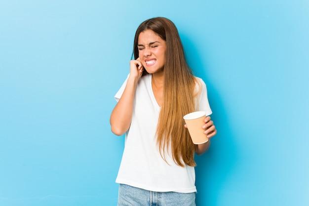 Jovens bonitas mulher caucasiana, segurando um café para viagem, cobrindo as orelhas com as mãos.