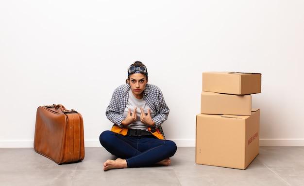 Jovens bonitas mulher com bagagem de couro e caixas de papelão