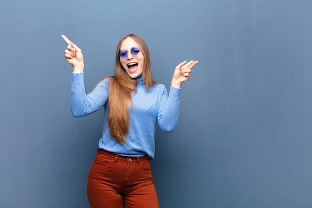 Jovens bonitas mulher com óculos de sol contra a parede azul com um espaço de cópia