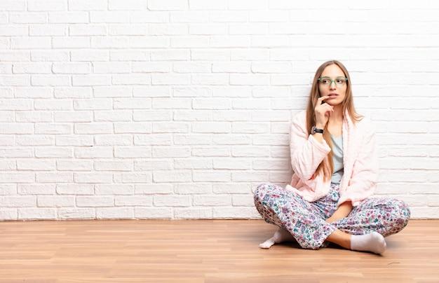 Jovens bonitas mulher com olhar surpreso, nervoso, preocupado ou assustado, olhando para o lado em direção ao espaço da cópia