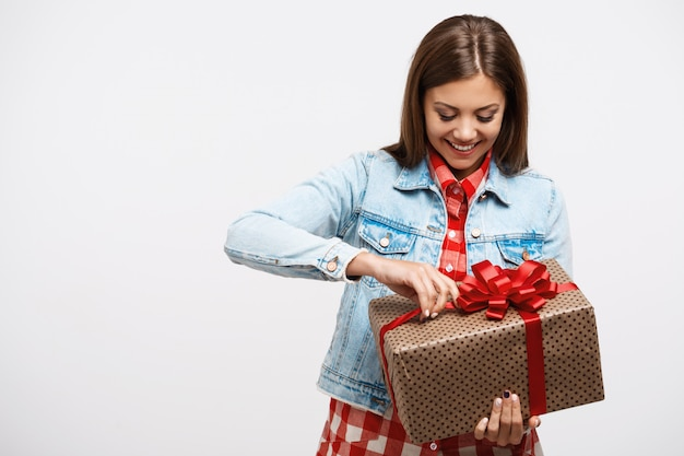Jovens bonitas mulher com roupa de primavera moda abrindo o presente de aniversário