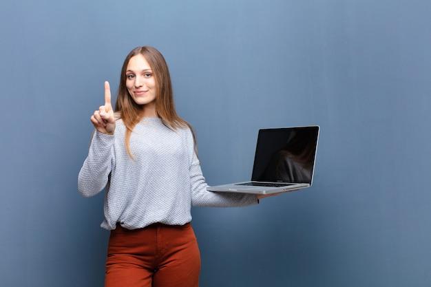 Jovens bonitas mulher com uma parede de laptop azul com uma copyspace