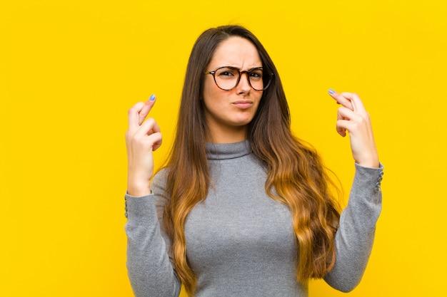 Jovens bonitas mulher cruzando os dedos ansiosamente e esperando a boa sorte com um conceito de emprego ou negócio de olhar preocupado