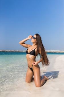 Jovens bonitas mulher de biquíni na praia tropical, sentado de joelhos