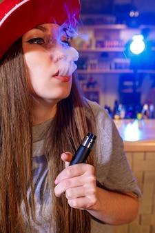 Jovens bonitas mulher de boné vermelho fumam um cigarro eletrônico na loja vape