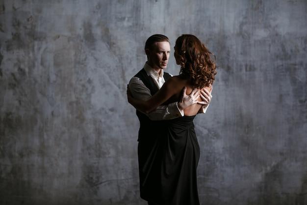 Jovens bonitas mulher de vestido preto e homem dançam valse