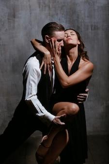 Jovens bonitas mulher de vestido preto e homem dançando tango