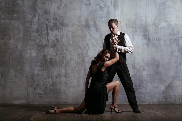 Jovens bonitas mulher de vestido preto e homem dançar tango