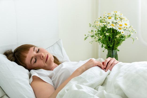 Jovens bonitas mulher dormindo no quarto com margaridas flores