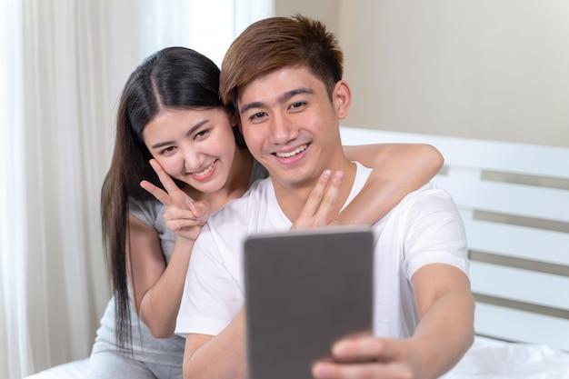 Jovens bonitas mulher e homem bonito, deitado no quarto em casa vídeo chamando alguém